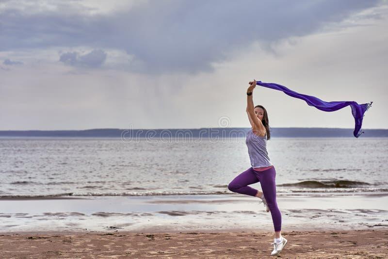 Junge d?nne brunette Frau, die beim R?tteln w?hrend springt, einen blauen Schal in ihren H?nden halten Eine Frau nimmt an Gymnast stockfotografie