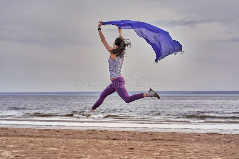 Junge d?nne brunette Frau, die beim R?tteln w?hrend springt, einen blauen Schal in ihren H?nden halten Eine Frau nimmt an Gymnast lizenzfreie stockfotografie