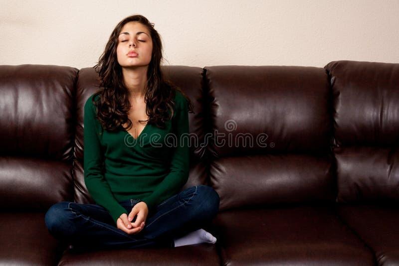 Junge Dame auf einer ledernen Couch stockfoto