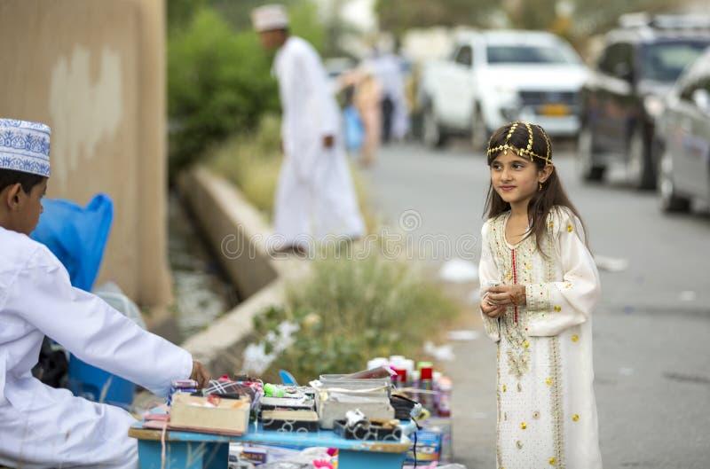 Junge Dame in der traditionellen Ausstattung von Oman an einem Spielzeugmarkt an Tannen stockfotos
