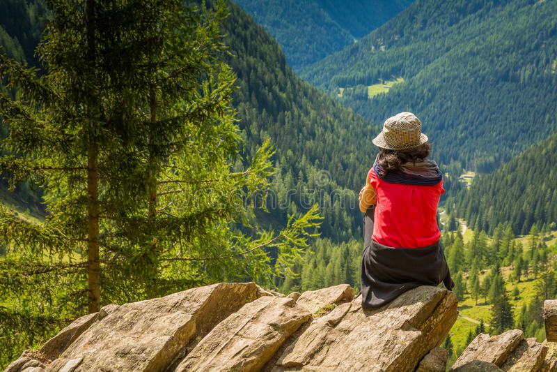 Junge Dame des Reisenden, die auf die Gebirgs- und enjoyng Talansicht steht Rabbinertal, Trentino Alto Adige, Italien lizenzfreie stockbilder