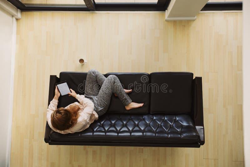 Junge Dame, die auf einer Couch unter Verwendung der digitalen Tablette sich entspannt lizenzfreie stockbilder