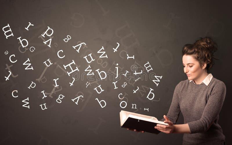 Junge Dame, die Buch mit Buchstaben hält lizenzfreies stockbild