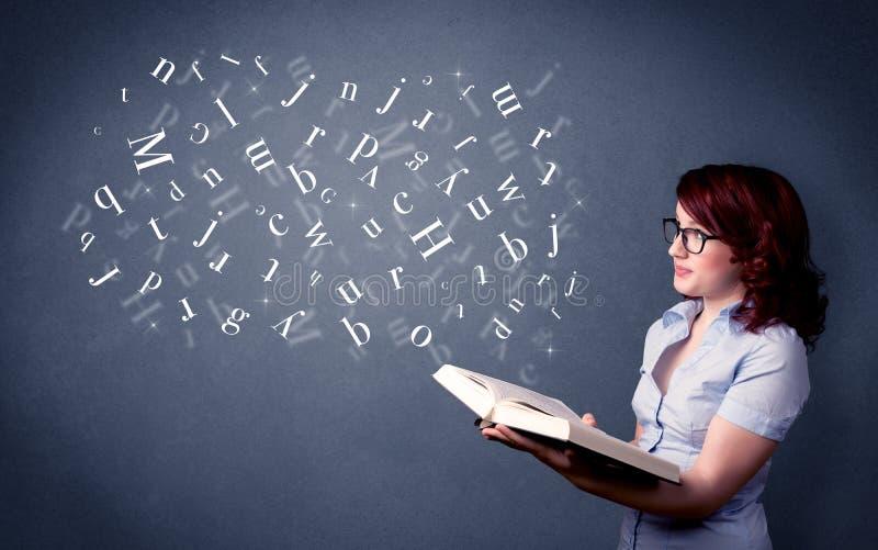 Junge Dame, die Buch mit Buchstaben hält lizenzfreies stockfoto