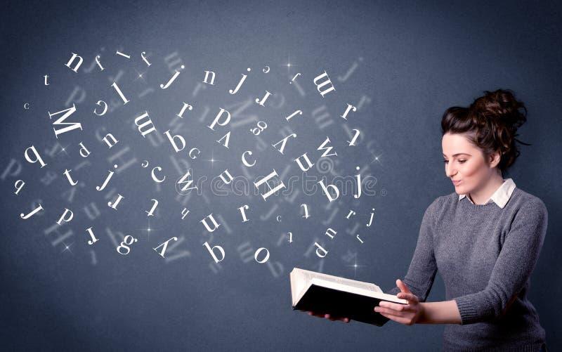 Junge Dame, die Buch mit Buchstaben hält lizenzfreie stockfotos