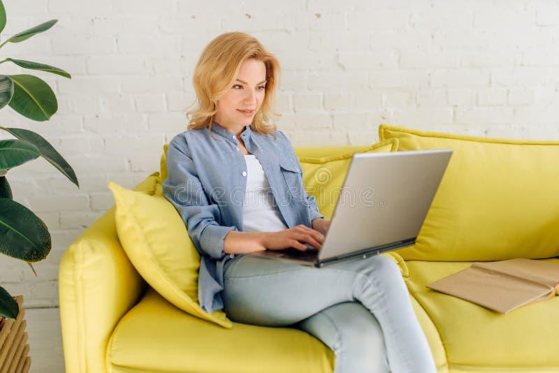 Junge Dame, die ein Buch auf gem?tlicher gelber Couch liest lizenzfreies stockbild