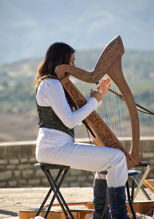 Junge Dame, die eine Harfe spielt stockbilder