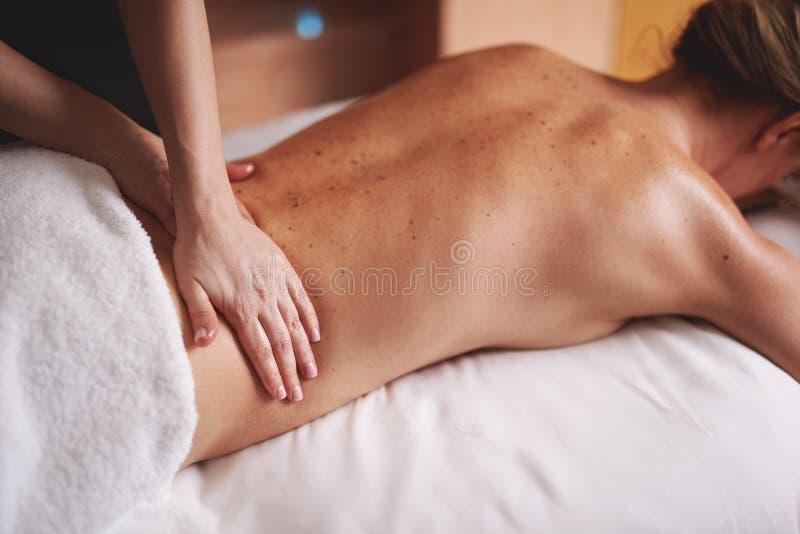 Junge Dame, die Massage der Lende im Badekurortsalon hat stockbilder