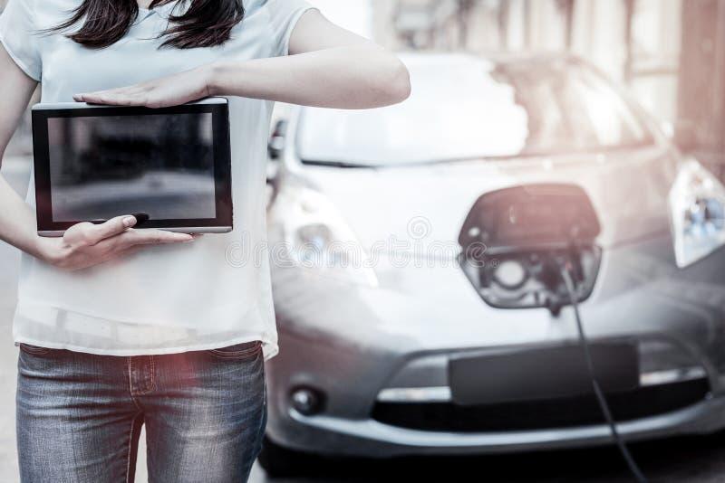 Junge Dame, die mit Berührungsfläche mit Elektroauto im Hintergrund aufwirft lizenzfreies stockfoto