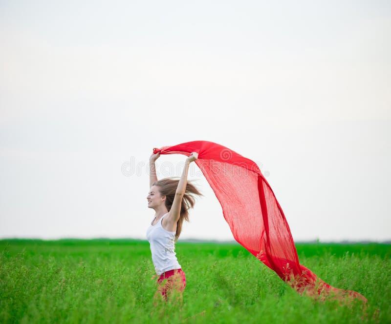 Junge Dame, die mit Gewebe auf dem grünen Gebiet läuft Frau mit Schal stockfotografie