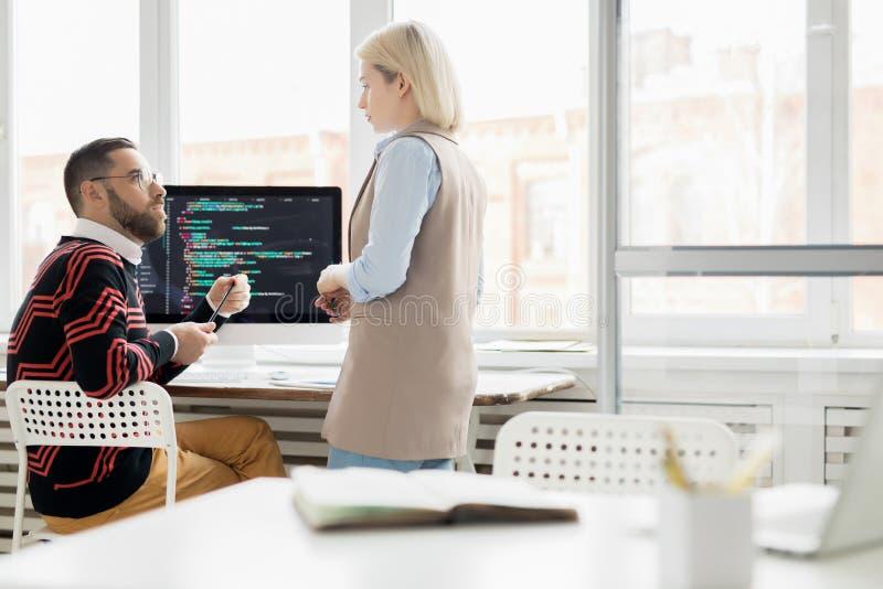 Junge Dame, die mit Programmierer im Büro arbeitet lizenzfreie stockbilder