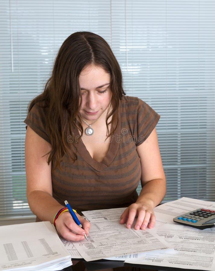 Junge Dame, die USA-Steuerformular 1040 für 2012 vorbereitet lizenzfreies stockbild
