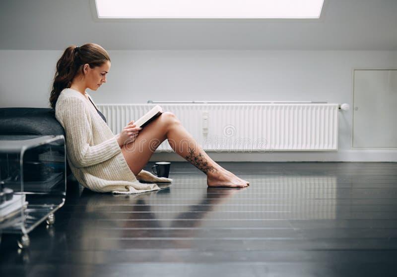 Junge Dame, die zu Hause ein Buch liest stockbild