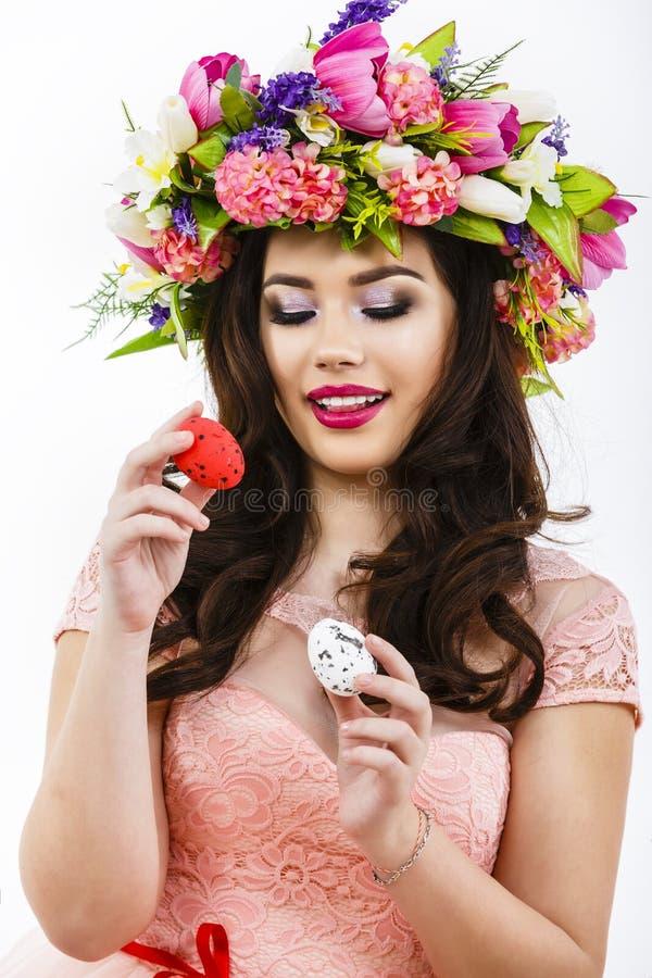 Junge Dame, die zwei schlägt, färbte Eier, Ostern-Dekor stockbilder