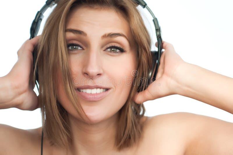 Junge Dame in hörender Musik der großen Kopfhörer lizenzfreie stockfotografie
