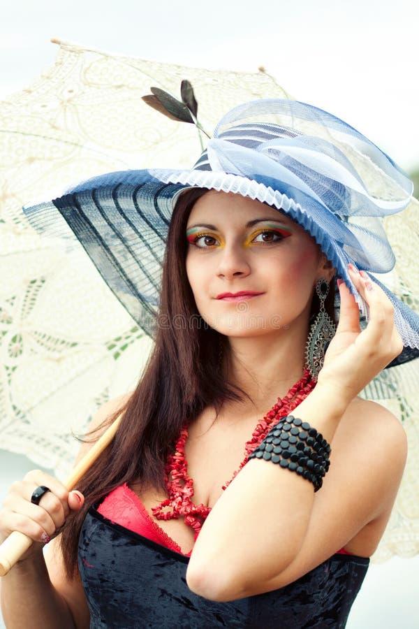 Junge Dame im Hut mit einem Regenschirm stockfotos