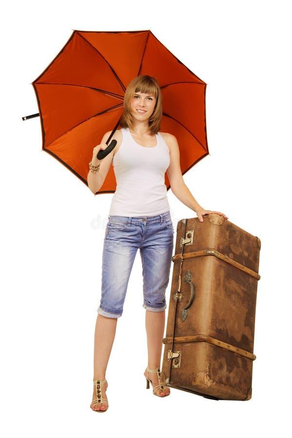 Junge Dame mit einem Regenschirm und einem suitecase lizenzfreies stockfoto
