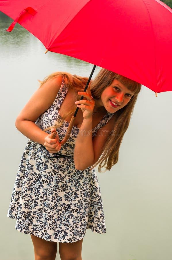 Junge Dame mit rotem Regenschirm nahe dem Teich lizenzfreie stockfotografie