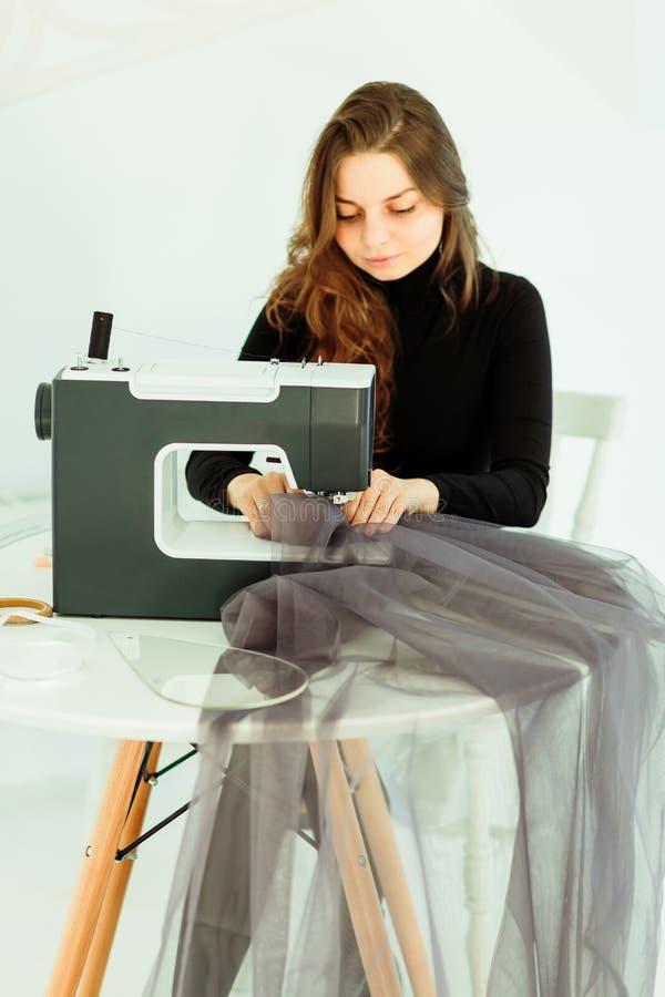 Junge Damenschneiderinfrau näht Kleidung auf Nähmaschine lizenzfreie stockbilder
