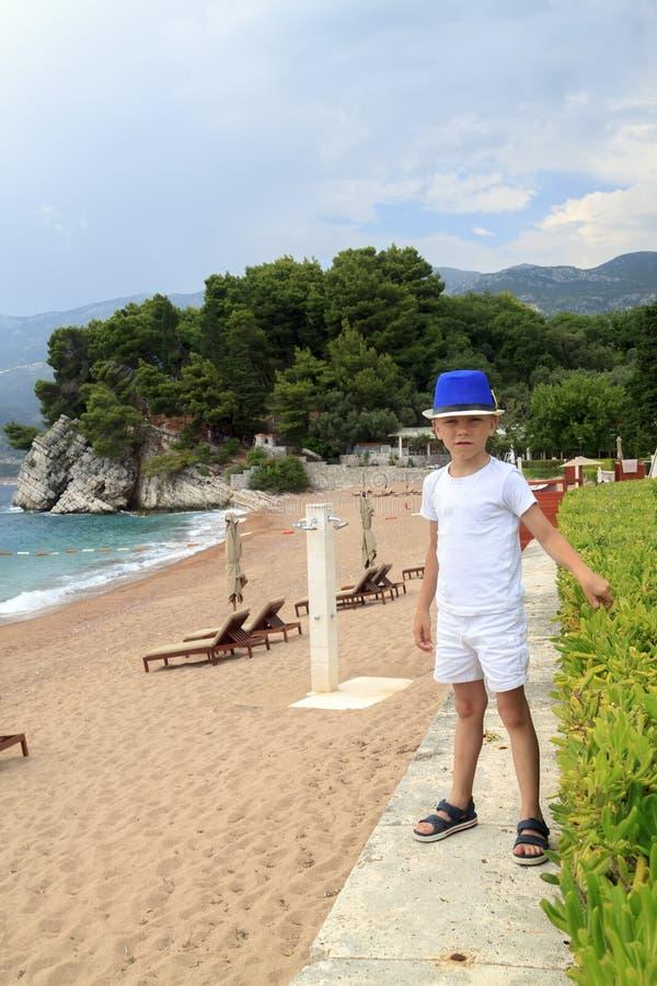 Junge in den blauen Hutwegen auf dem Strand in Milocher-Park nahe Budva stockfoto