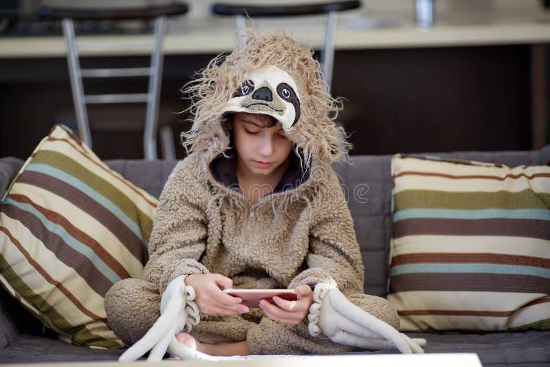 Junge in den Trägheitspyjamas, die Handy spielen lizenzfreie stockfotos
