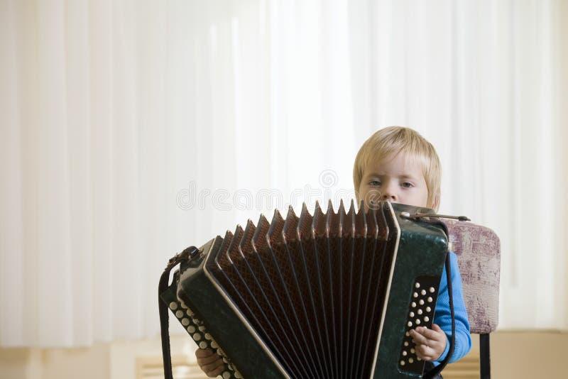 Junge, der Akkordeon spielt stockbild