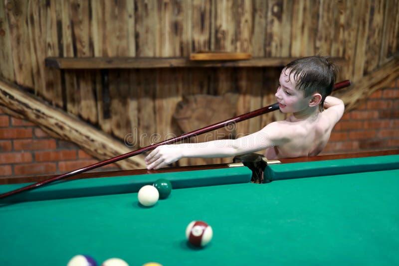 Junge, der amerikanisches Billard spielt lizenzfreie stockfotografie
