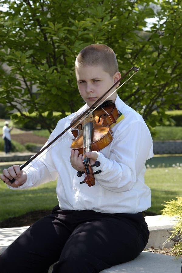 Junge, der außerhalb des Spielens der Viola sitzt stockfotos