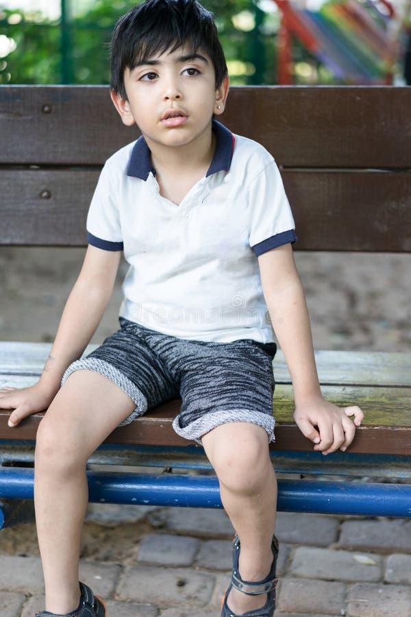 Junge, der auf Bank sitzt stockbild