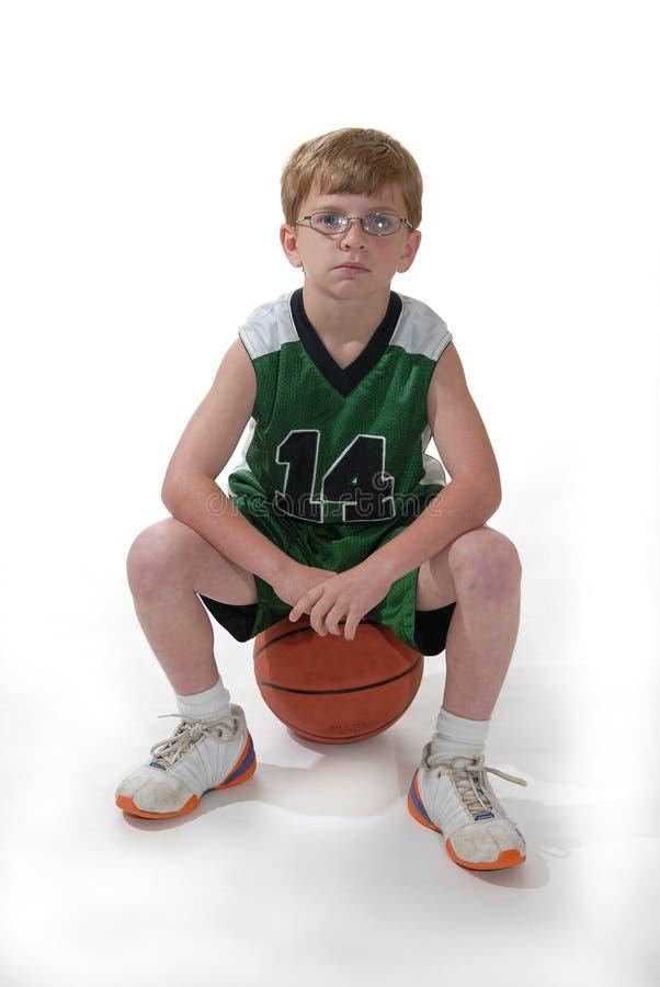 Junge, der auf Basketball sitzt lizenzfreie stockfotos