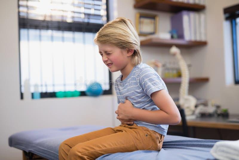 Junge, der auf Bett mit Magenschmerzen sitzt lizenzfreies stockbild