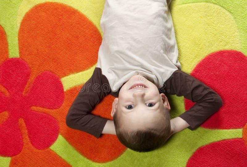 Junge, der auf buntem Teppich liegt stockfotografie