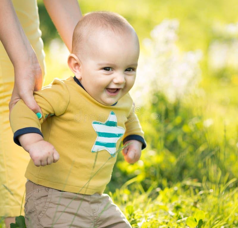 Junge, der auf das Gras durch Elternteil geht stockbilder