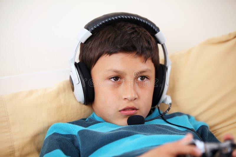 Junge, der auf das Spielen des Videospiels sich konzentriert stockfoto
