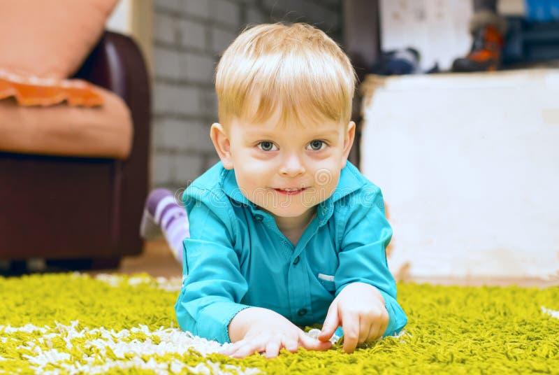 Junge, der auf dem Fußboden liegt lizenzfreie stockfotos