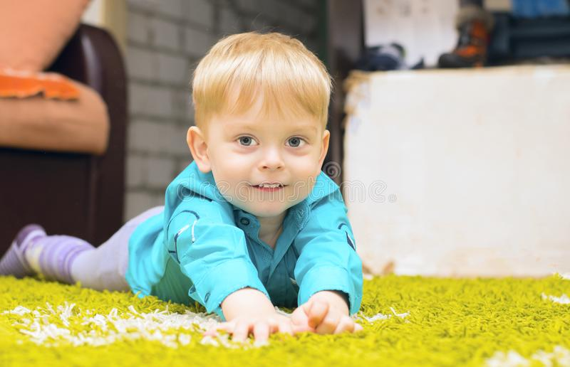 Junge, der auf dem Fußboden liegt stockfoto