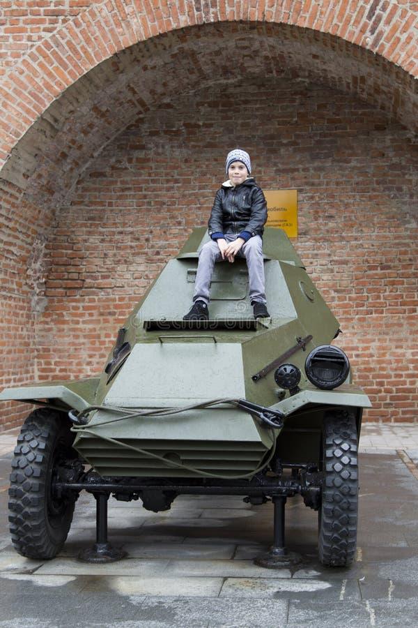 Junge, der auf dem Panzerkampfwagen im Kreml in Nischni Nowgorod, Russische Föderation sitzt lizenzfreie stockfotografie
