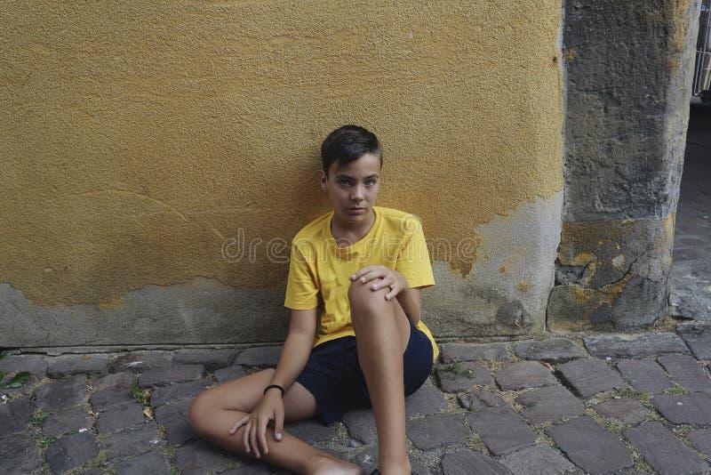 Junge, der auf dem Straßenboden sitzt lizenzfreie stockbilder