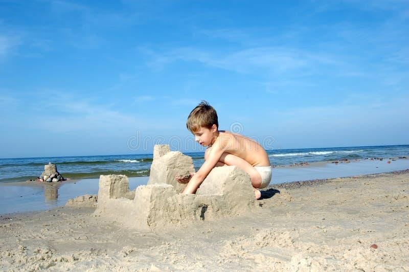 Junge, der auf dem Strand spielt lizenzfreie stockfotografie