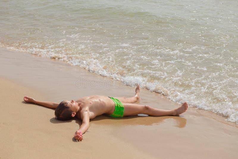 Junge, der auf dem Strand und dem Sonnen liegt stockfotografie