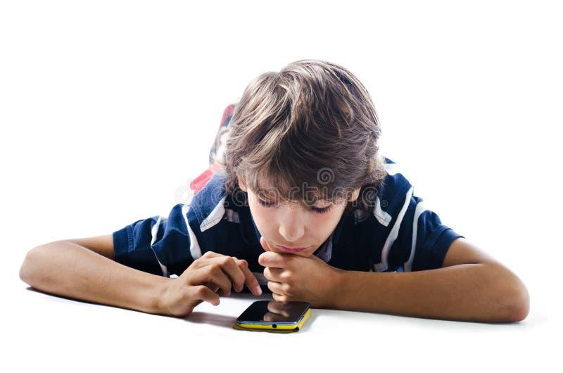 Junge, der auf den Boden unter Verwendung des Handys legt stockfotos