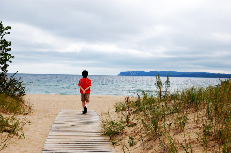 Junge, der auf den Strand setzen geht lizenzfreies stockfoto