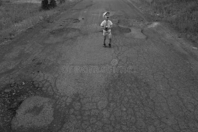 Junge, der auf die gebrochene Straße geht stockbild
