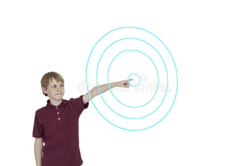 Junge, der auf digital entworfene konzentrische Kreise über weißem Hintergrund zeigt stockfoto