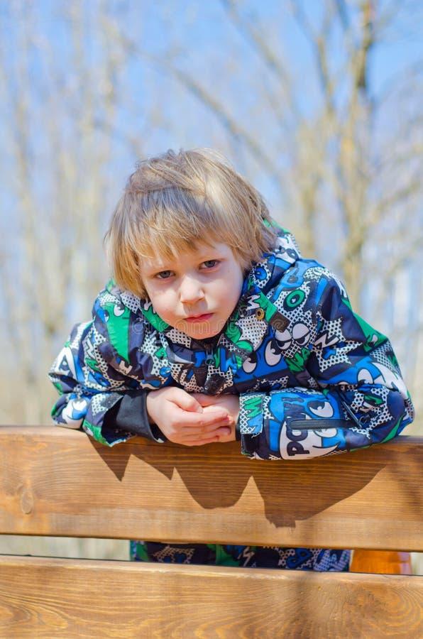 Junge, der auf einer Bank sitzt lizenzfreies stockfoto