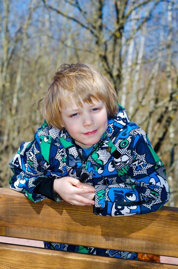 Junge, der auf einer Bank sitzt stockbilder