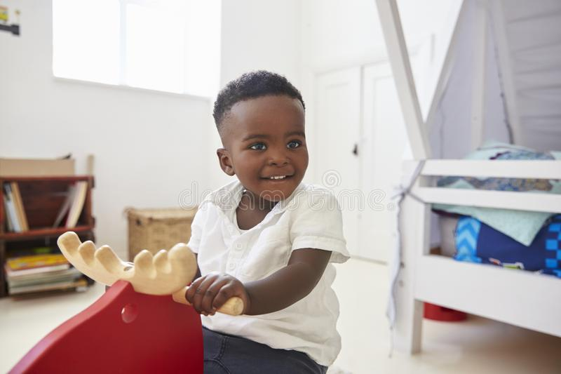 Junge, der auf Fahrt auf Toy In Playroom sitzt stockbild