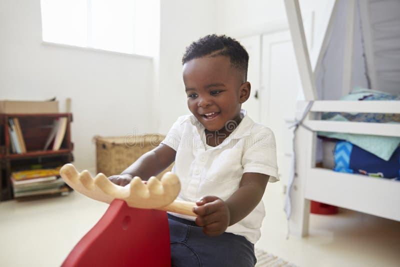Junge, der auf Fahrt auf Toy In Playroom sitzt stockbilder