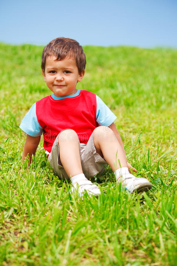 Junge, der auf Gras sitzt lizenzfreie stockfotos