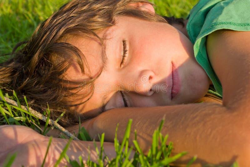 Junge, der auf Gras träumt lizenzfreies stockbild